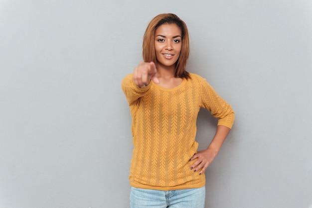 Sonriente joven mujer africana en suéter y jeans apuntando