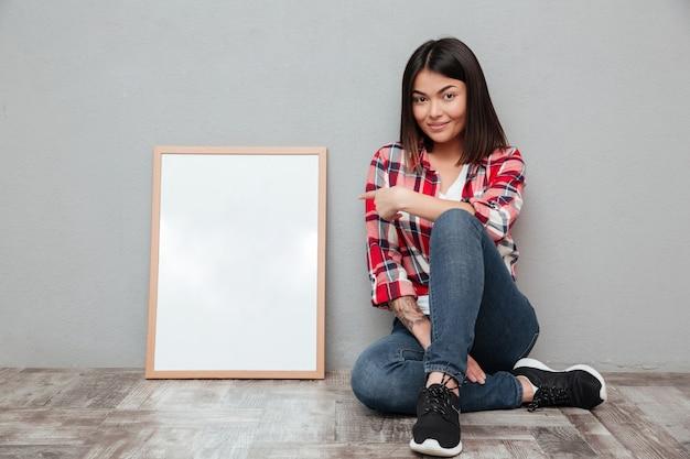 Sonriente joven mujer asiática sentada cerca de copyspace en blanco y señalando