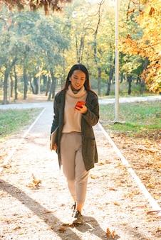 Sonriente joven mujer asiática vistiendo abrigo caminando al aire libre en el parque, escuchando música con auriculares, sosteniendo el teléfono móvil, llevando portátil