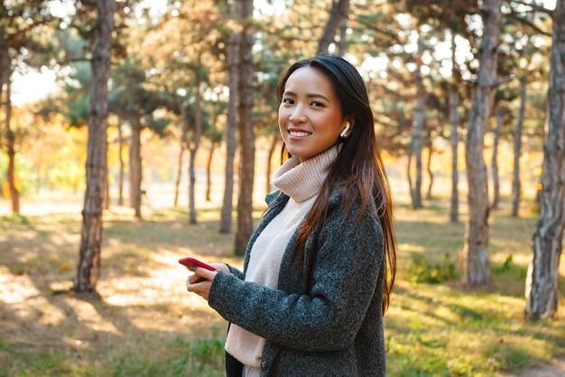Sonriente joven mujer asiática vistiendo abrigo caminando al aire libre en el parque, escuchando música con auriculares, sosteniendo el teléfono móvil
