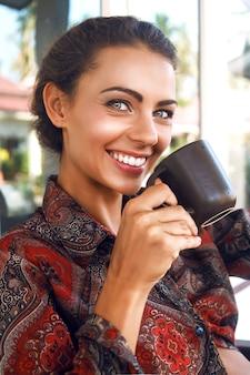 Sonriente joven mujer bastante positiva bebiendo su café matutino favorito, tiene un bonito maquillaje natural y una piel perfecta.