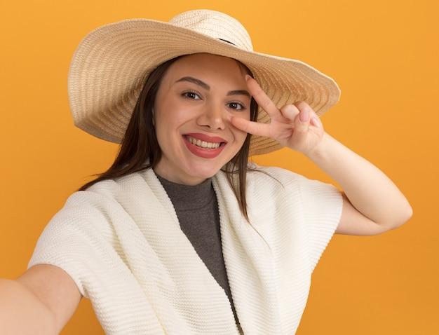 Sonriente joven mujer bonita con sombrero de playa mirando al frente estirando la mano hacia el frente mostrando el símbolo de signo v cerca del ojo aislado en la pared naranja