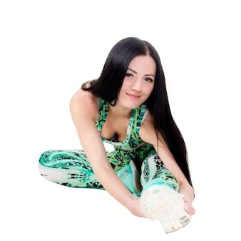 Sonriente joven mujer con cabello largo sentado hace estiramientos