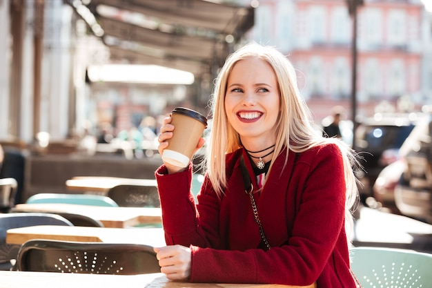 Sonriente joven mujer caucásica sentado en la cafetería al aire libre