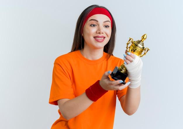 Sonriente joven mujer deportiva con diadema y muñequeras con muñeca lesionada envuelta en una venda sosteniendo y mirando la copa ganadora aislada en la pared blanca con espacio de copia