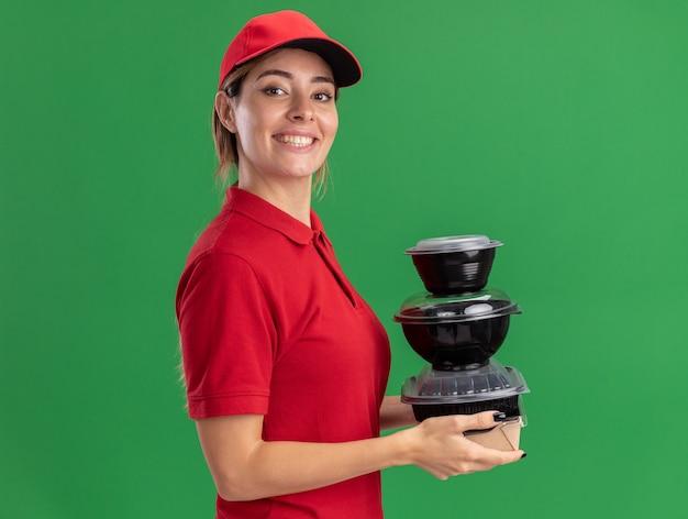 Sonriente joven mujer de entrega bonita en uniforme se encuentra de lado sosteniendo contenedores de comida en paquete de comida aislado