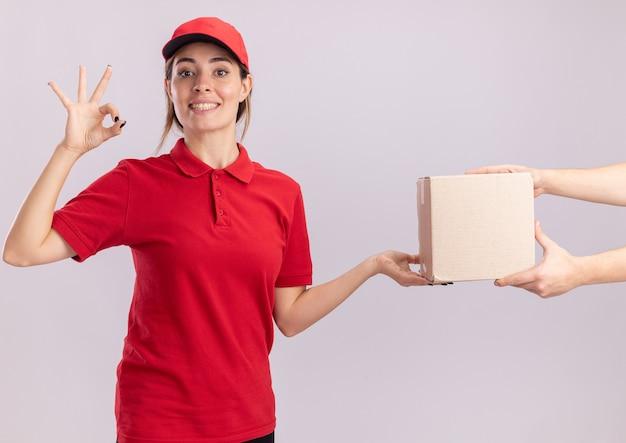 Sonriente joven mujer de entrega bonita en uniforme gestos ok signo de mano y da caja de cartón a alguien aislado