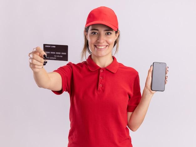 Sonriente joven mujer de entrega bonita en uniforme con tarjeta de crédito y teléfono aislado en la pared blanca