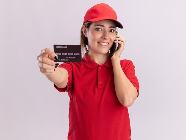 Sonriente joven mujer de entrega bonita en uniforme tiene tarjeta de crédito y habla por teléfono aislado en la pared blanca