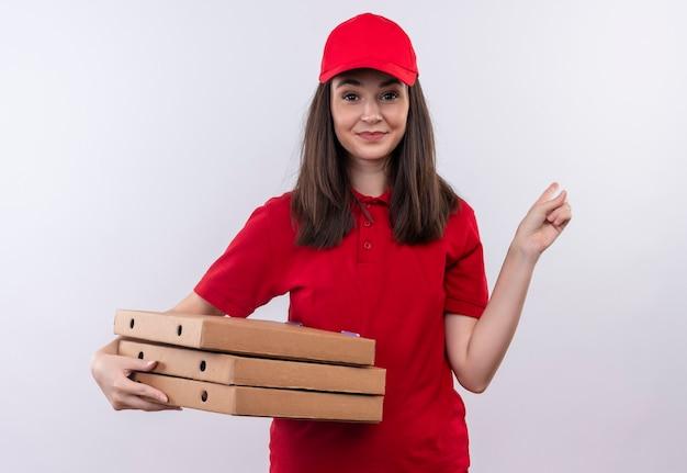 Sonriente joven mujer de entrega con camiseta roja en gorra roja sosteniendo la caja de pizza y apunta hacia atrás en la pared blanca aislada