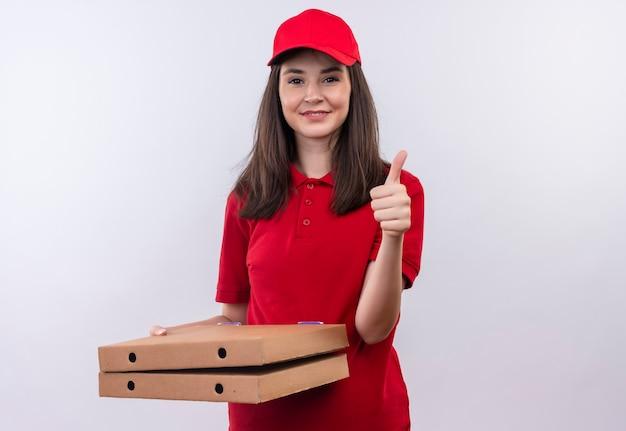 Sonriente joven mujer de entrega con camiseta roja en gorra roja sosteniendo la caja de pizza y mostrando los pulgares hacia arriba en la pared blanca aislada