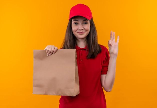 Sonriente joven mujer de entrega con camiseta roja en gorra roja sosteniendo el paquete y muestra gesto okey en pared amarilla aislada