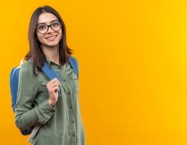 Sonriente joven mujer de la escuela con mochila con gafas