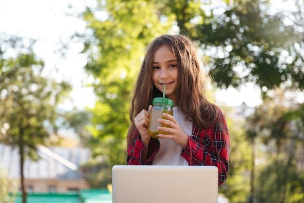 Sonriente joven mujer morena sentada en el parque con ordenador portátil