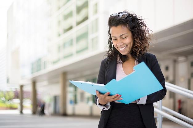 Sonriente joven mujer de negocios latinoamericana leyendo algunos documentos en la calle. espacio para texto.