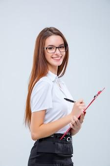 Sonriente joven mujer de negocios en vasos con lápiz y portapapeles