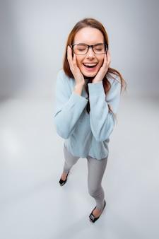 Sonriente a joven mujer de negocios en vasos sobre un fondo gris. vista superior