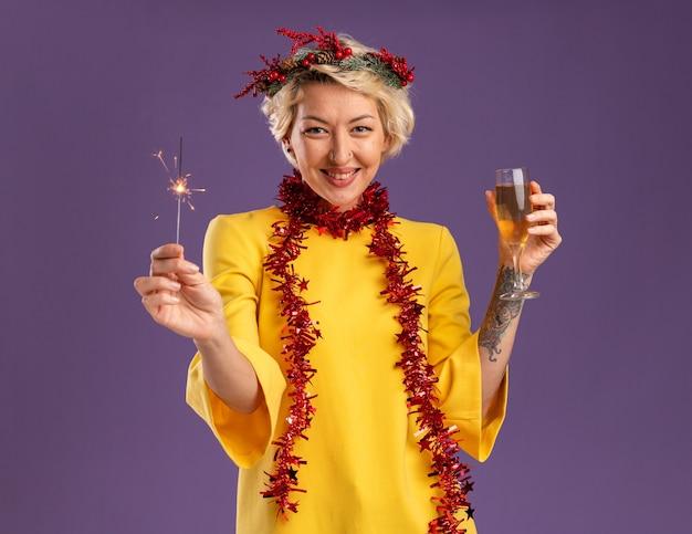 Sonriente joven mujer rubia con corona de navidad y guirnalda de oropel alrededor del cuello sosteniendo bengala de vacaciones y copa de champán mirando a cámara aislada sobre fondo púrpura