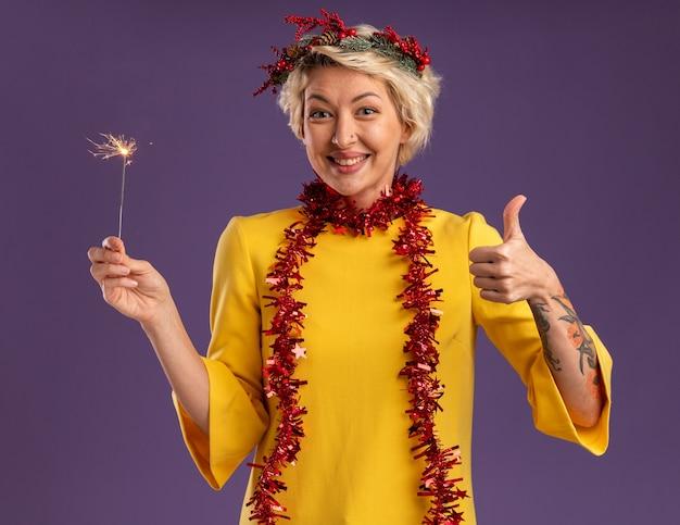Sonriente joven mujer rubia con corona de navidad y guirnalda de oropel alrededor del cuello sosteniendo bengala de vacaciones mirando a cámara mostrando el pulgar hacia arriba aislado sobre fondo púrpura