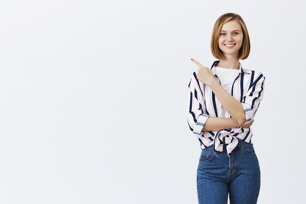 Sonriente joven mujer segura apuntando hacia la esquina superior izquierda en copyspace