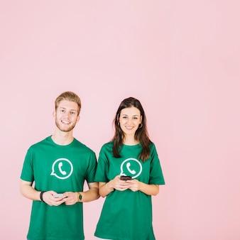 Sonriente joven y mujer sosteniendo teléfono móvil contra el fondo rosa