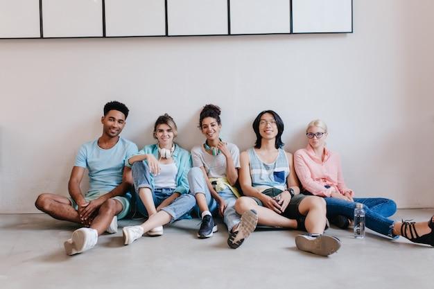 Sonriente joven negro con camisa azul sentado en el suelo junto a sus amigos. retrato interior de estudiantes internacionales esperando exámenes en el suelo.