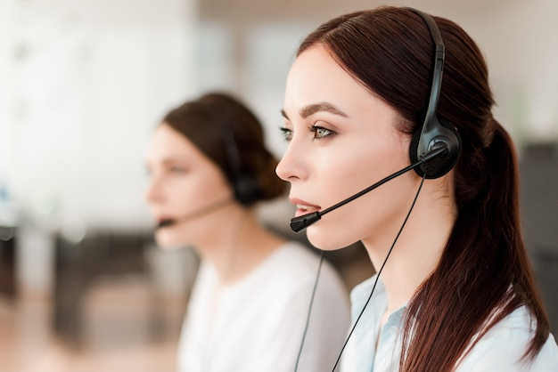 Sonriente joven oficinista con un auricular respondiendo en un centro de llamadas