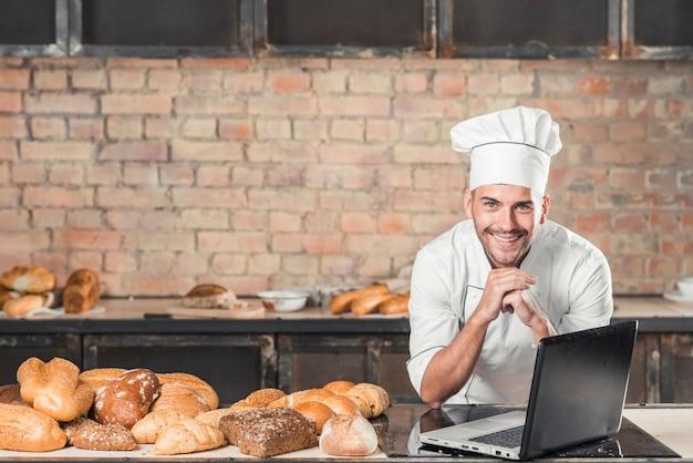 Sonriente joven panadero masculino apoyándose en la mesa con variedad de pan y portátil