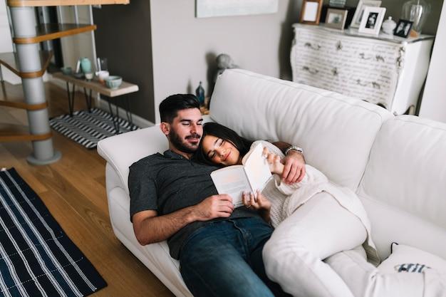 Sonriente joven pareja acostado en el sofá leyendo el libro en la sala de estar