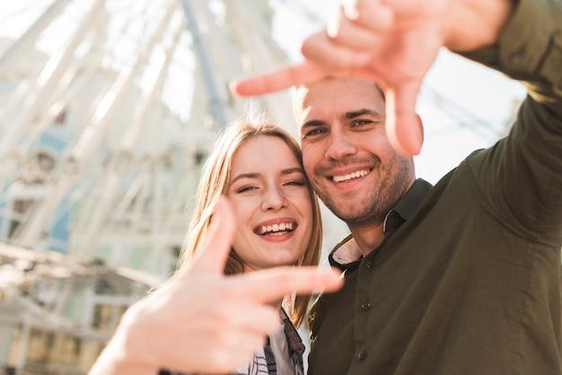 Sonriente joven pareja amorosa haciendo marco a mano