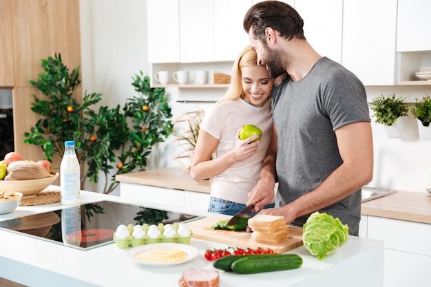 Sonriente joven pareja amorosa de pie en la cocina y cocinar