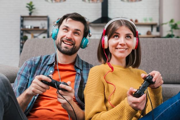 Sonriente joven pareja con auriculares en la cabeza jugando al videojuego