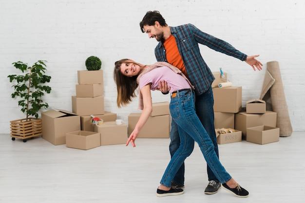 Sonriente joven pareja bailando en cajas de cartón en su nueva casa