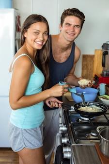 Sonriente joven pareja cocinando comida en la cocina