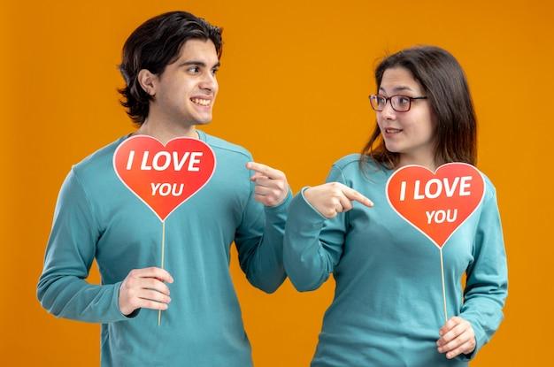 Sonriente joven pareja en el día de san valentín sosteniendo y apunta al corazón rojo en un palo con te amo texto aislado sobre fondo naranja