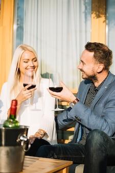 Sonriente joven pareja disfrutando de bebidas juntos