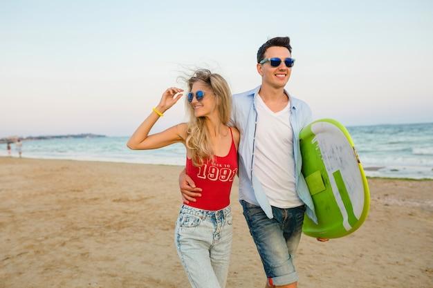 Sonriente joven pareja divirtiéndose en la playa caminando con tabla de surf