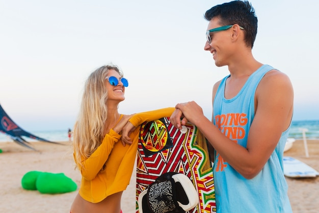 Sonriente joven pareja divirtiéndose en la playa con tabla de kitesurf en vacaciones de verano