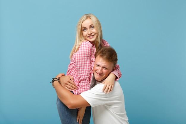 Sonriente joven pareja dos amigos chico chica en blanco rosa diseño en blanco vacío camisetas posando