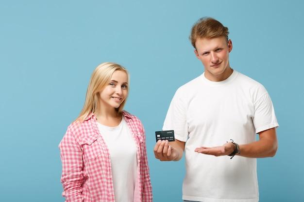 Sonriente joven pareja dos amigos chico y mujer en blanco rosa camisetas en blanco vacías posando