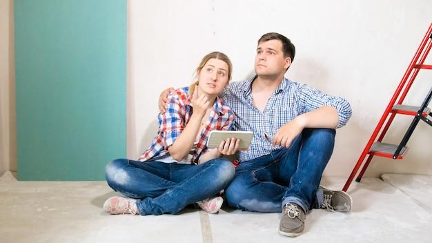 Sonriente joven pareja eligiendo el diseño de su nueva casa en la computadora de la tableta.