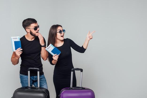Sonriente joven pareja feliz con maletas y billete alrededor aislado en blanco