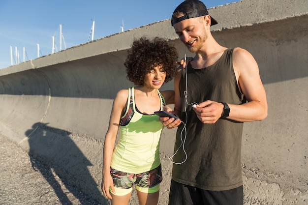 Sonriente joven pareja fitness escuchando música