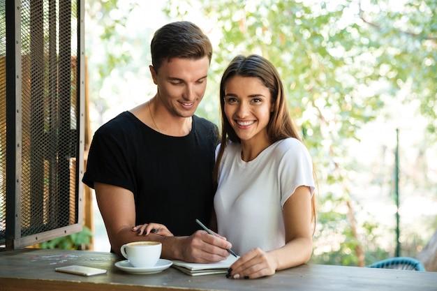 Sonriente joven pareja haciendo notas en un libro de texto juntos