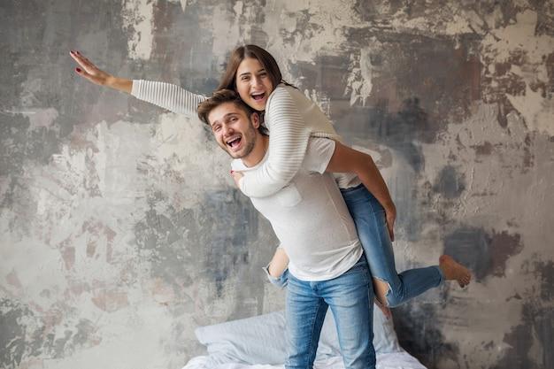 Sonriente joven pareja jugando en la cama en casa en ropa casual, hombre y mujer divirtiéndose juntos, emoción positiva loca, feliz, sosteniendo la mano