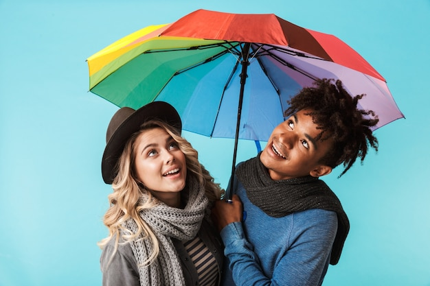 Sonriente joven pareja multirracial con bufandas de pie con un paraguas aislado sobre pared azul