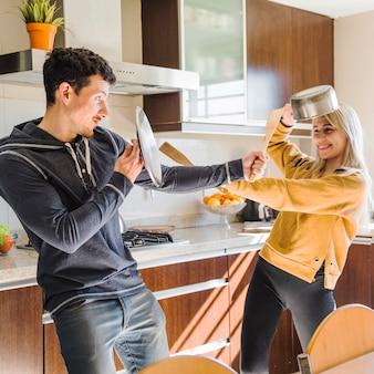 Sonriente joven pareja peleando con utensilio en la cocina