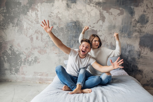 Sonriente joven pareja sentada en la cama en casa en ropa casual, hombre y mujer divirtiéndose juntos, loca emoción positiva, feliz, levantando las manos