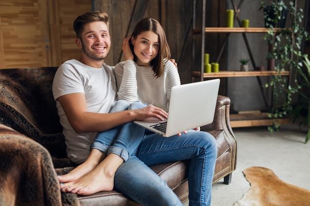 Sonriente joven pareja sentada en el sofá en casa en ropa casual