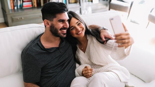Sonriente joven pareja sentada en el sofá tomando selfie